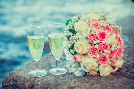 glass of champagne and a bouquet of the bride on a background of water photo