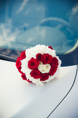 bridal bouquet of red and white roses lying on the hood of a car photo