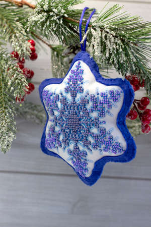 Textile christmas decoration snowflake with blue beaded embroidery, DIY handmade close up