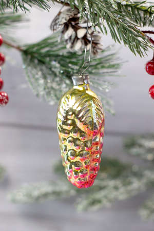 Old soviet decoration on the Christmas tree, glass toy pine cone close up on light background
