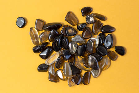 Macro shooting of collection natural rock set of morion, smoky quartz gem mineral stones on yellow background