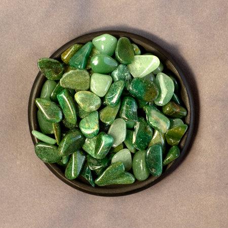 Macroshooting of natural mineral rock specimen - tumbled green aventurine gemstone on black plate