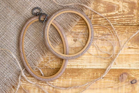 Embroidery hoop, oval and round frames on rough grey linen, top view close up