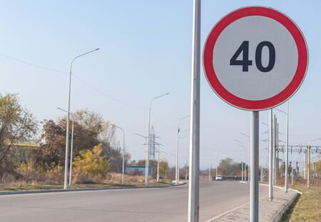 Speed limit sign of 40 kilometers per hour on a pillar near an asphalt road with lanterns