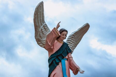 The statue where Jesus Christ raised his right hand up with his index finger and has two wings on his back. Against the background of blue sky with clouds
