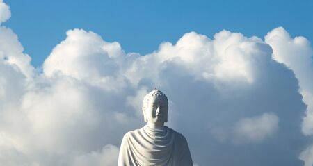 Big white buddha statue against the blue sky and huge white clouds