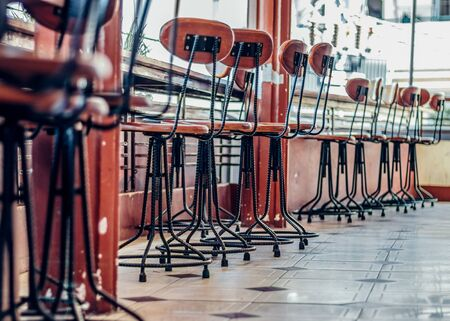 Bar stools made of metal and wood stand on the tiled floor along the bar counter. Bottom view