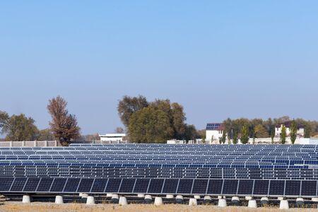Muchas filas de paneles solares en una estación de energía renovable. Fondo de cielo azul Foto de archivo