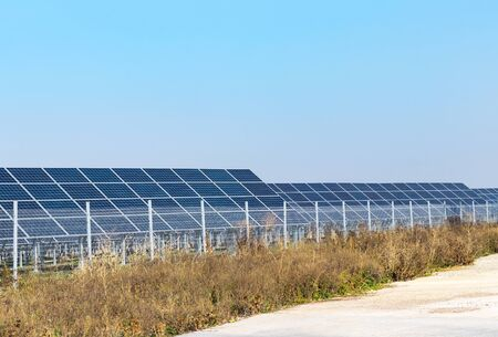 Rows of solar panels behind a fence of a renewable energy station. Background of blue sky and dry grass