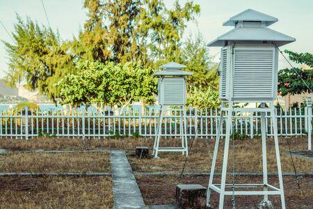 Dos cabinas psicrométricas en la estación meteorológica. Con el telón de fondo de una valla blanca y árboles