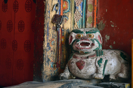 animal figurines: Ancient wooden figure of a traditional Tibetan snow lion at the door in the Buddhist Hemis Monastery, Himalayas, India.