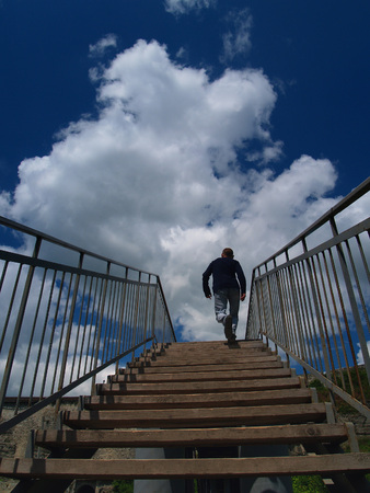 Old wooden staircase with wide steps and metal railing, stretching into the blue sky with huge white cloud, up the stairs a man running as if running away into the heavens.