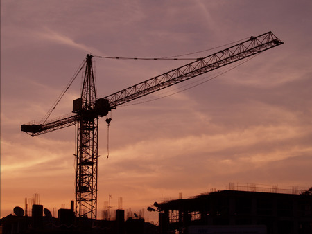 The black silhouette of a high crane and unfinished house on the pink background sunset sky, building in the city.