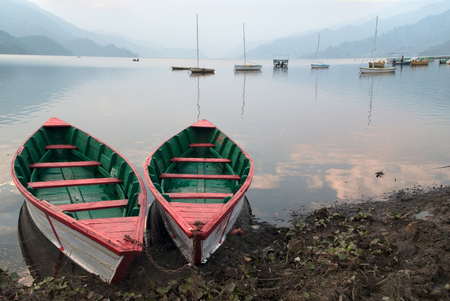 phewa: Two boats of bright colors: white linen and green and red inside, parked on the shore of the lake, in the background many other boats, dawn, Pokhara, Nepal.
