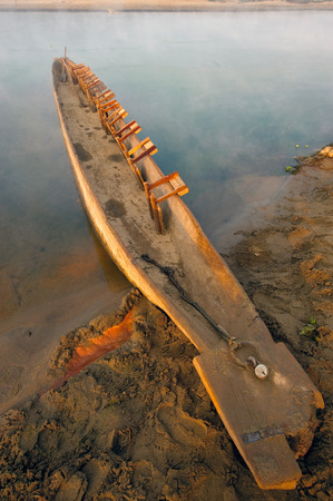 mode made: A homemade wooden fishing boat canoe on the river bank, diagonally in the frame, is colored by the light of the sunrise in orange, on the blue background of the river, Chitwan, Nepal. Stock Photo