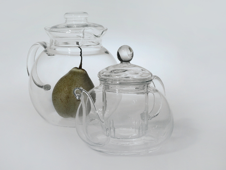Two glass transparent teapots stand next to each other, inside a large round teapot a green pear, a light background. Stock Photo
