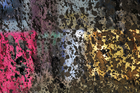 unevenly: Abstraction of color and light: crimson, pink, yellow, brown rectangles with black blobs, unevenly lit by the rays of the sun. Stock Photo