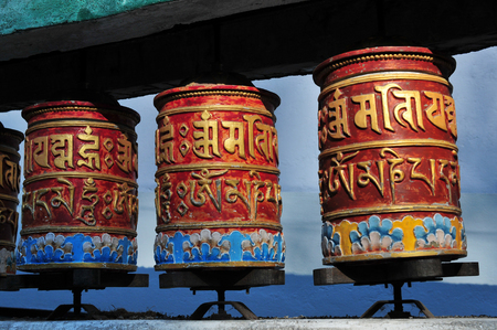 orison: Three Buddhist prayer drums of red color with yellow hieroglyphs mantra against a blue sky background on a clear day, Tibet.