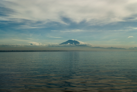 Volcano Mount Batur from the side of the lagoon: in the foreground there is a surface of water, in the distance a mountain, over which white clouds diverge in different directions, Bali, Indonesia.