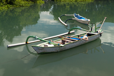 shallop: Balinese wooden boat with a one-sided counterweight, white, tied with a rope to the shore, in the background is another boat, reflections in the water, Bali, Indonesia.