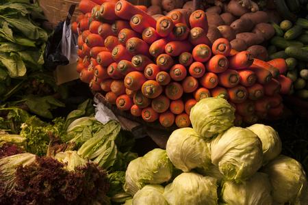 Still life with vegetables on the village market: a slide of green cabbage, a basket of bright orange carrots, lettuce leaves.
