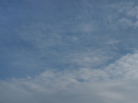 diagonally: White cirrus clouds diagonally on matte blue sky background as a large feather.