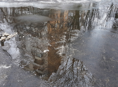 Gloomy gray diagonal reflection of a large house in brown puddle on wet asphalt, bare branches of a tree, the snow melts.