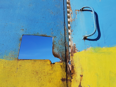 The old rusty door, decorated in the colors of the Ukrainian flag: blue on top and yellow from below, in the middle of the hole, which shows the blue sky and the right metal handle, street art.