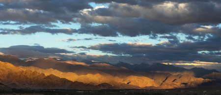 Panoramic view of the sunset in the mountain valley: twilight, part of a mountain chain painted rays of the sun in yellow, huge blue sky with a beautiful drawing of a dark gray and blue clouds, Tibet. Stock Photo