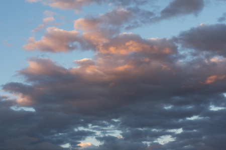 Many cumulonimbus clouds in the blue sky, sunset rays paint white and gray clouds in a gentle pink color. Stock Photo