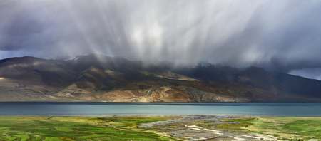Thunderstorm on the high mountain lake Tso Moriri: the sun rays create a beautiful effect in the clouds above the lake, the blue water surface and green fields, Ladakh, Northern India.