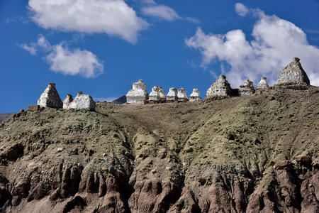 sierra: White Buddhist Tibetan ancient stupa on the crest of a high mountain under a blue sky with clouds, Tibet, Northern India.
