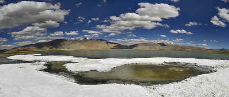 salinity: Shores of Tso Kara lake, covered with snow-white crust rock salt, in which individual puddles salt water, blue lagoon surface, mountains in the background, the Himalayas, India.