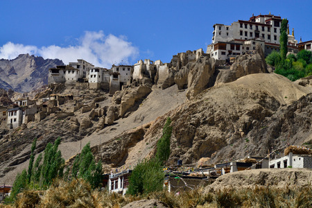Ancient Tibetan Buddhist monastery Lamayuru Gonpa: huge tall gong buildings stand on a mountain ridge among green trees, Ladakh, Northern India.
