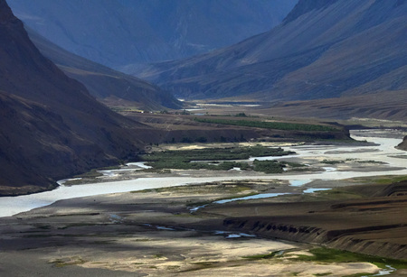The river bed of the high mountains: a water stream flowing among the high banks among the sandbanks, small green fields and dark mountain slopes, Himalayas.