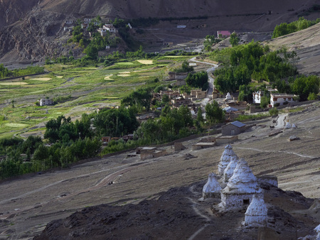 tibetan house: Ancient white Tibetan stupas in a row on a mountainside and an ancient Buddhist monastery over a mountain village, Tibet, Himalayas. Stock Photo