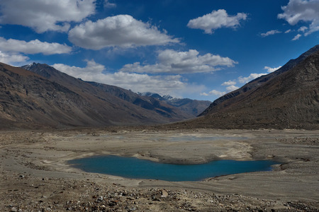 High mountains glacial lake, oblong water body bright blue color water surface in the midst of a mountain valley with chains of brown peaks, the Himalayas, Tibet, Northern India. Stock Photo