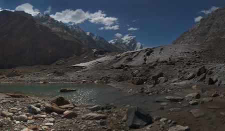 mountainous: Huge high mountains glacier of the Himalayas: powerful brown moraines of the sediments descend from the mountainous icy peaks, the foreground is an elongated lake with muddy gray water, photopanorama, Northern India. Stock Photo