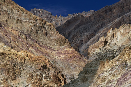 interspersed: Beautiful colored high mountains: cliffs of pink, brown, green interspersed with each other.