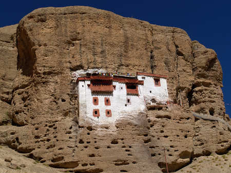 Buddhist monastery inside a huge rock, a white gong building with brown windows built in the mountains pits, Kargil, Northern India.