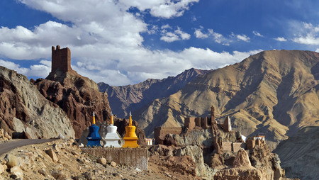 The ruins of ancient Tibetan monastery Basgo Gonpa, burgundy ruins of the old fortress and colored new Buddhist stupas in the foreground, Ladakh, Northern India.