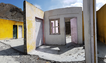 Walls of a ruined house without a roof, yellow, pink and white surfaces with empty apertures of windows and doors, blue sky. Stock Photo
