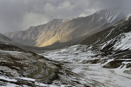 Snow covered mountain valley with a country road serpentine on the left slope.