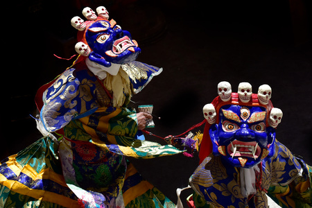 Two Buddhist manahs in the blue ancient masks of Mahakala perform the Dance of Tsam, the Sacred Dance of Masks, on black background. Stock Photo