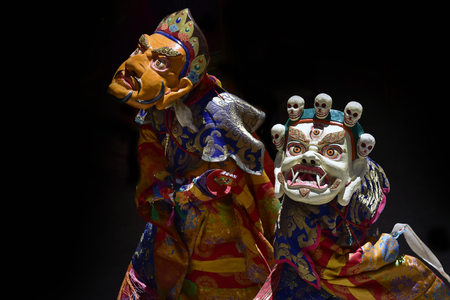 Lama dance in Masks, Cham Dance, yellow and white ancient masks and fine Tibetan clothes on a black background, Buddhist mystery, Ladakh, Himalayas. Stock Photo