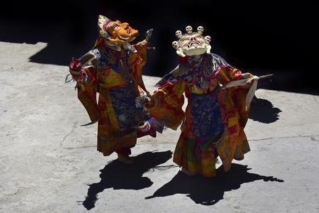 Tibetan monks perform the dynamic Cham Dance, the Mask Dance to the bright illuminated playground of the monastery, Karcha Gonpa, Zanskar, Northern India.