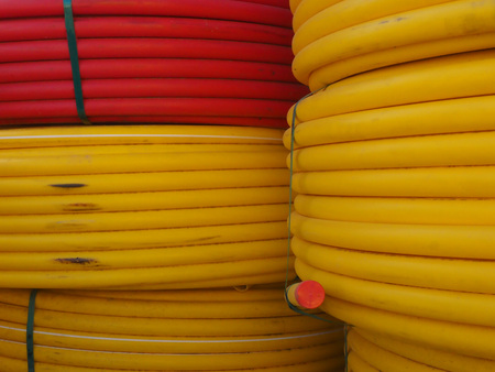 Thick electric cables coils are bright yellow and bright red, curled into smooth circles.