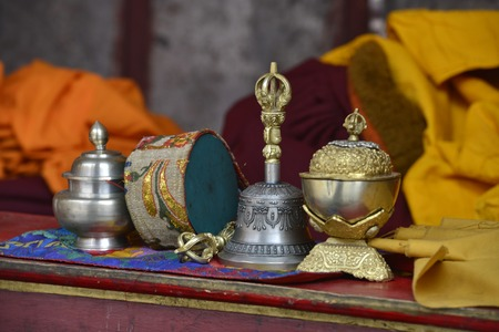 Ritual Buddhist objects for puja: a Tibetan bell, a drum and silver bowls on the prayer table of a lama. Stock Photo