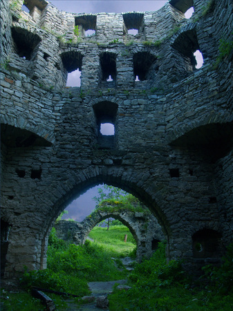 Wall of an ancient stone fortress: a masonry with empty window apertures, at the bottom of an arch among which the bright green grass and bushes, the Middle Ages grows.