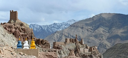 Road to the Buddhist monastery of Basgo: in the foreground there stupas, in the background among the rocks there are ruins of the monastery in the background of the mountains, Ladakh, Himalayas. Stock Photo